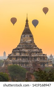 Many tourists on Shwesandaw Pagoda and in hot air balloons watching rising sun in Bagan, Myanmar