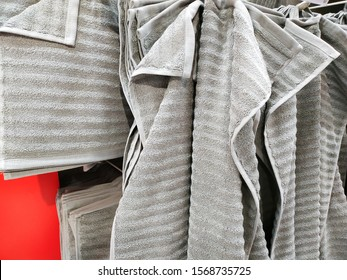 many towels hanging on the hook for sale in housewares shop.