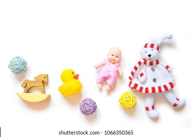 Many toys for children's games on a white background. Rocking wooden horse, yellow rubber duck, doll and teddy bear. Mockup, free space for text
