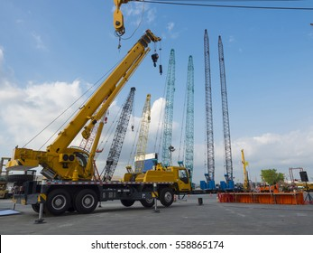 many Truck and Crane in yard site consist of lifting, pulley, sling, derrick are ready for construction