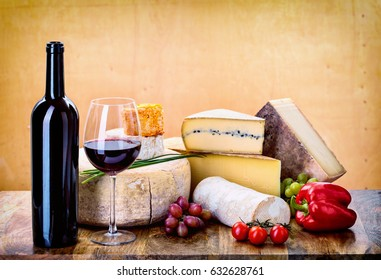 many types of french cheese - rondin de brebis, ossau-iraty, camembert, comte, vieux, tomme de chevre, langres, morbier, margalet with vegetables and bottle of wine and a glass