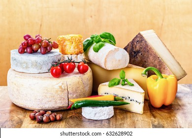 many types of french cheeses with basil, tomatoes and peppers - ossau-iraty, langres, tomme de chevre, rondin de brebis, camembert, morbier, comte, vieux
