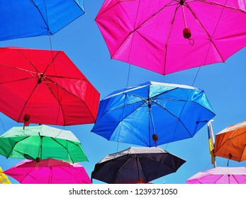 Many unicolore umbrellas in many colors are stacked in the sky, as a roof at a folk festival on tenerife