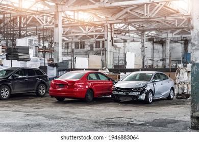 Muchos autos alterados y destrozados desconocidos después del accidente de tráfico en la estación de servicio de restauración de mantenimiento de garaje interior. Venta al por mayor de vehículos de salvamento de seguros. Centro del taller de daños por restos de carrocería automática