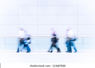 Many unrecognizable business people in a fair hall, intentional motion blur, blue tinted high resolution stock photo