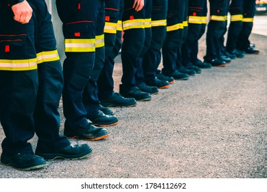 Many unrecognizable firefighters lined up in reflective pants.