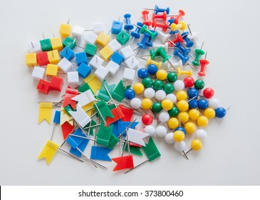 Many varicolored plastic push pins, different forms. Selective focus
