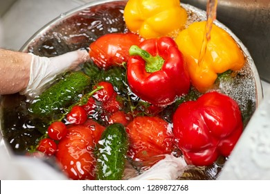 Many vegetables sinking in a bowl of water. Chef dipping vegetables into water.