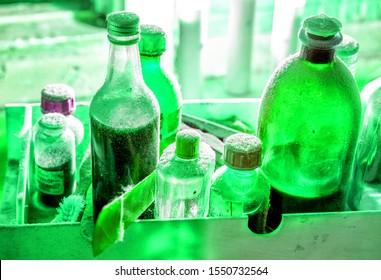 many vintage green glass bottles in lab