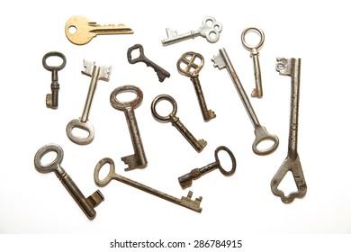 Many vintage keys to the safe on a white background