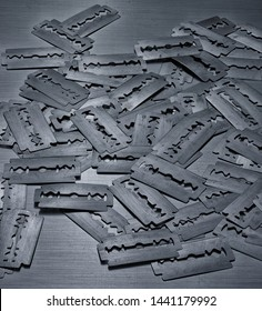 Many vintage razor blades on steel background, macro. Old worn razor blades on an iron table.