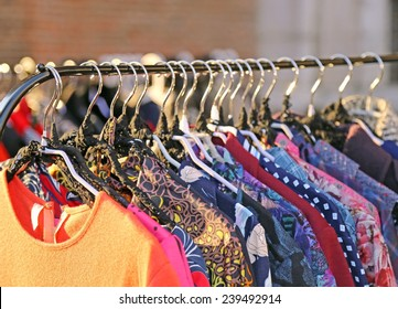 Many vintage style clothes  for sale at an outdoor flea market