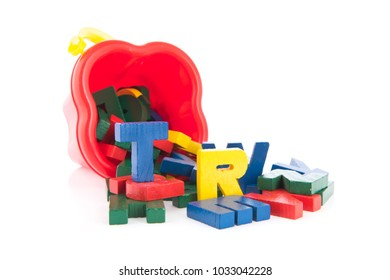 Many vintage wooden letters in toy bucket isolated over white background