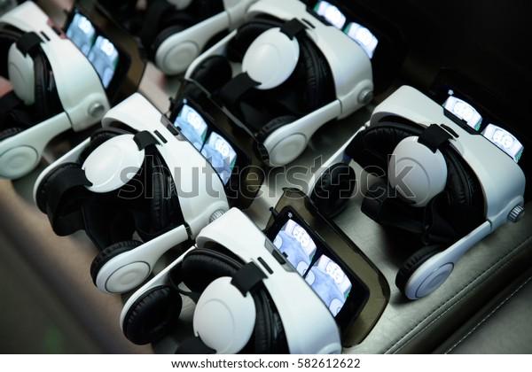 many virtual reality VR helmets on dark background