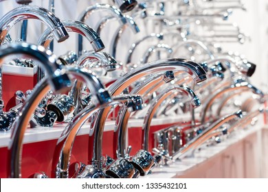 Many water mixers for baths, kitchens. Many samples mounted on the wall.