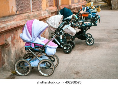 many wheels of strollers for toddlers parked near a stone wall