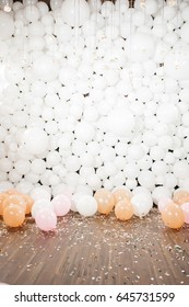 Many white balloons lie on the floor in the hall