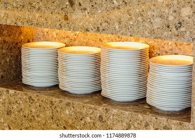 Many white ceramic bowls arranged in a marble cupboard