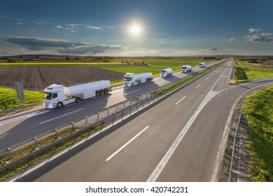 Many white gasoline tanker trucks in line driving towards the sun. Fast gasoline delivery on the freeway at beautiful idyllic day. Freight scene on the motorway near Belgrade, Serbia.
