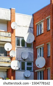 many white parabolic satellite antenna dishes hanged on wall of suburban perfab block of flats.