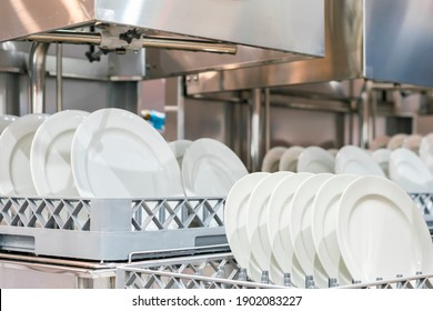many white plate on basket in automatic dishwasher machine for cleaning in kitchen room restaurant