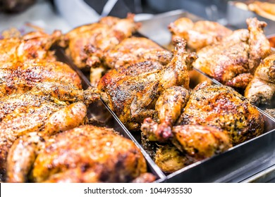 Many whole chicken roasted closeup on tray in deli display store shop grocery brown with herbs, golden skin, spices, crispy