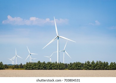 Many wind turbines spinning against a blue sky in southern Ontario, Canada