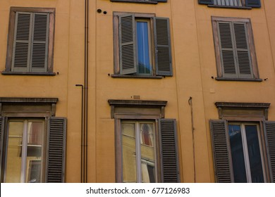 Many windows. Medieval facade. Window shutters. Architectural style of Italy