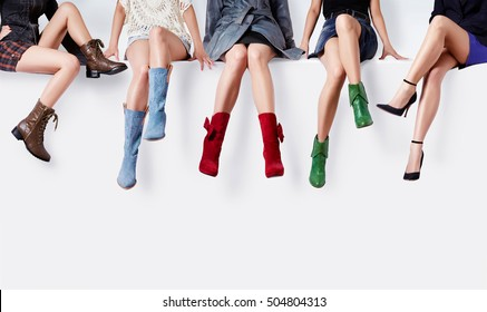 Many woman with colorful shoes sitting together. Fashion image with copy space.