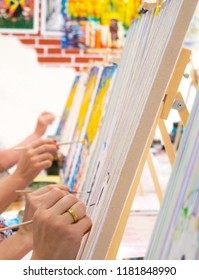 Many women of different ages drawing on canvases with brushes during masterclass in the art studio, hands only