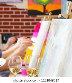 Many women of different ages drawing on canvases with brushes and drinking champagne during masterclass in the art studio, hands only