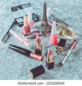 Many women's cosmetics for make-up and beauty care on a gray concrete background. Nail polish, perfume bottle, makeup shadows, lipstick, a statuette of the Eiffel Tower.