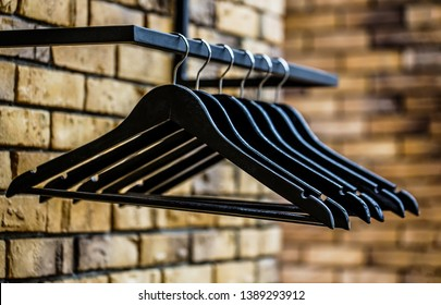 Many wooden black hangers on a rod. Store concept, sale, design, empty hangers. Black friday. Wooden coat hanger clothes. Fashionable different types of hanger. Wood Hangers coat.