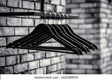Many wooden black hangers on a rod. Store concept, sale, design, empty hangers. Black friday. Black and white. Wooden coat hanger clothes. Fashionable different types of hanger. Wood Hangers coat.