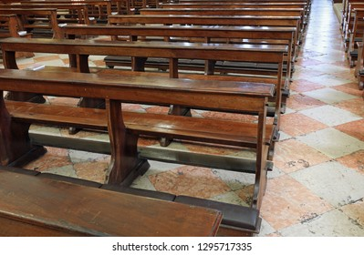 many wooden empty church desks also called pews  in th church without the faithful symptom of a profound serious religious crisis of current Catholicism