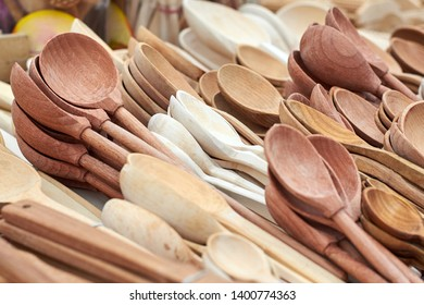 Many wooden spoons made from different types of wood on the market counter