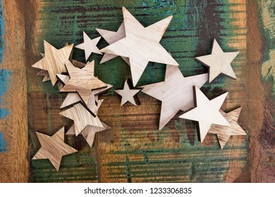 Many wooden stars lying on a colorful wooden table