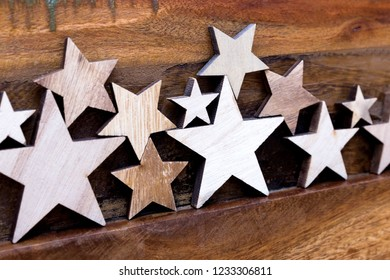 Many wooden stars standing on a wooden table