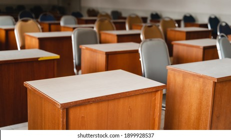 Many wooden tables and chairs well arranged in the university classroom but no student. Empty classroom with no student due to school being lockdown during COVID-19 pandemic.