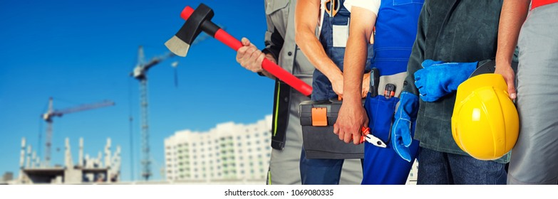 Many workers closeup with equipment on building background