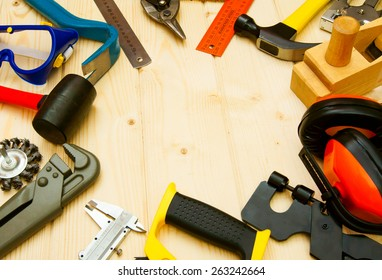 Many working tool. The different working tools (hammer, ruler, wrench and others) on a wooden background.