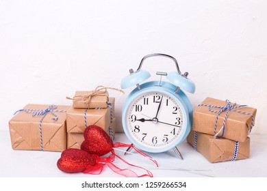 Many  wrapped boxes with presents, red heart  and blue alarm cllock on white textured background. Selective focus. Place for text.