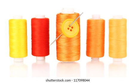 Many yellow bobbin with needle and buttons isolated on white