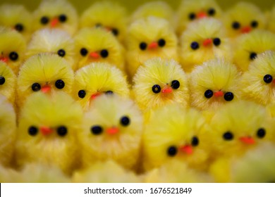 Many yellow, plastic chickens in a row at the supermarket with black eyes and orange beak