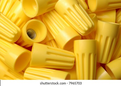 Many yellow wire nuts in a pile