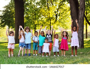 many young children of different races play together in the Park on the green fresh grass. The concept of ethnic friendship of different peoples.