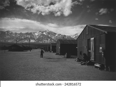 Manzanar Relocation Center, a World War II internment camp for Japanese Americans. A lone man walks on a barracks lined street in the winter of 1943. Photograph by Ansel Adams.