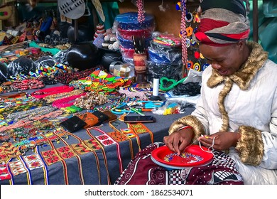 Manzini, Swaziland - October 30, 2019: African woman making a necklace with colorful beads and selling souvenirs, handicraft at Manzini market, Swaziland