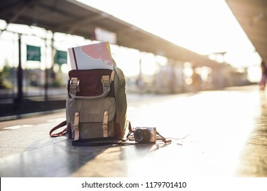 Map in Backpack ,Mobile phone with earphone and hat at the train station with a traveler.sun set, Travel concept.