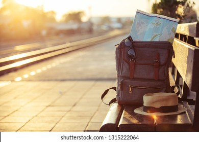Map in Backpack ,Sunglasses with hat at the train station with a traveler.sun set, Vintage Travel concept.